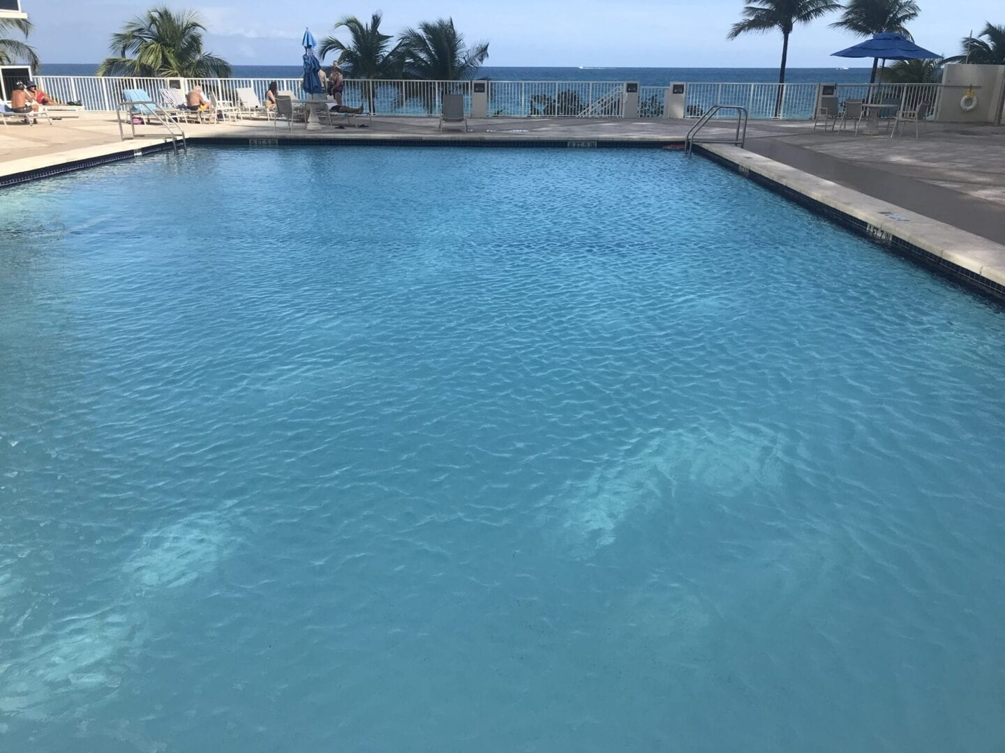 A wide pool enclosed by white fences with a view of the beach
