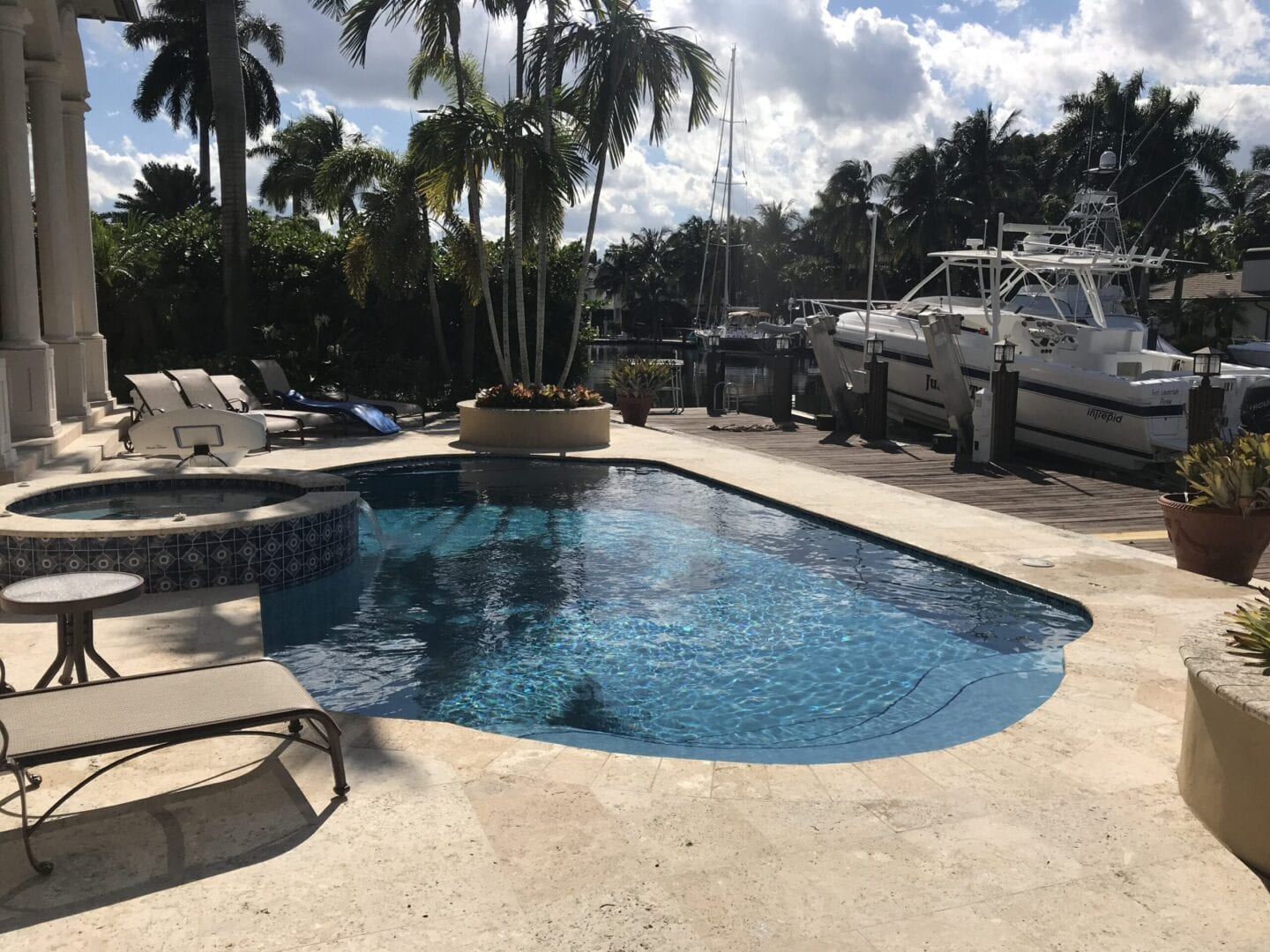 Small pool and Jacuzzi and a yacht parked nearby