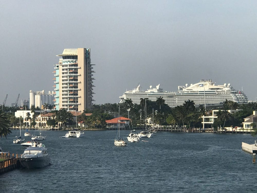 Florida bay with several yachts on the sea and some buildings in the background