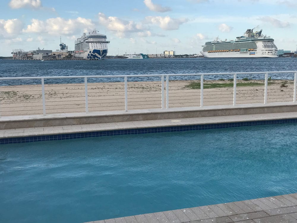 Rounded rectangle pool near the ocean with two big ships passing