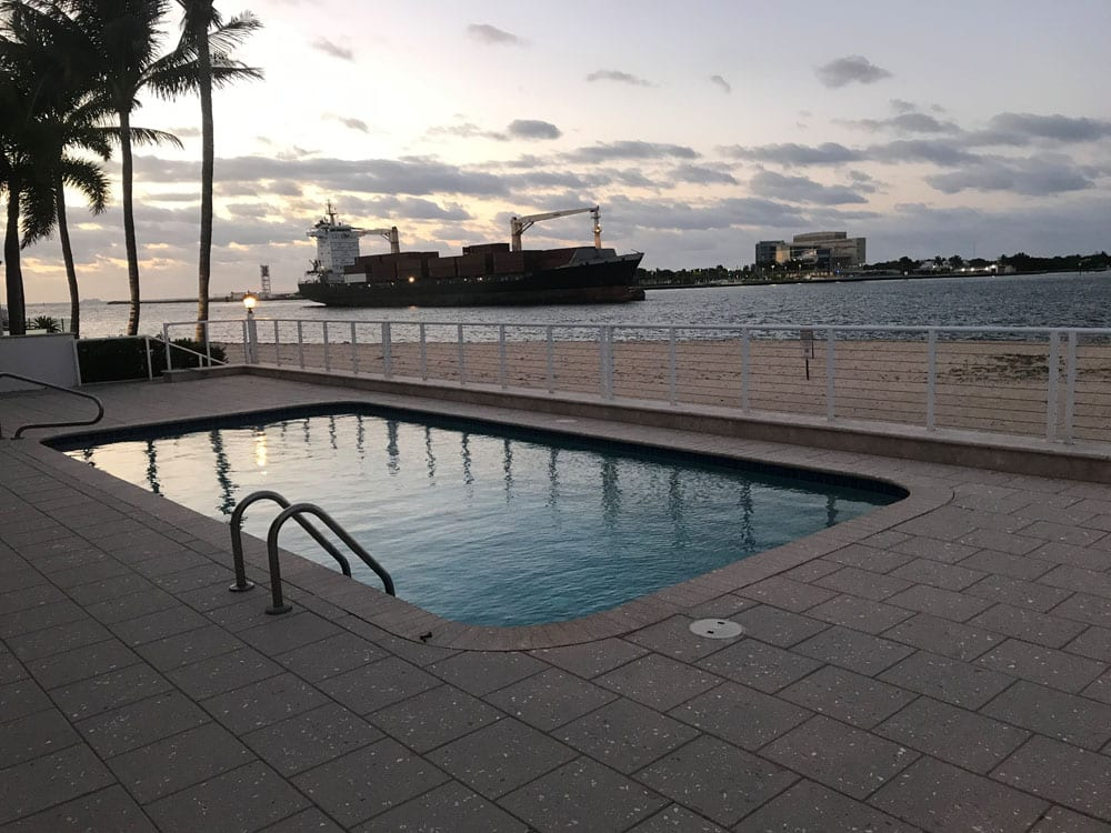 Rounded rectangle pool near the ocean with a cargo ship in the background