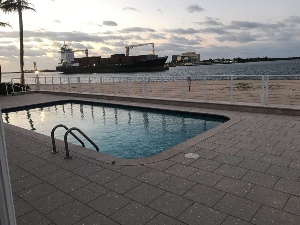 Rounded rectangle pool near the ocean with a cargo ship in the background (different angle)