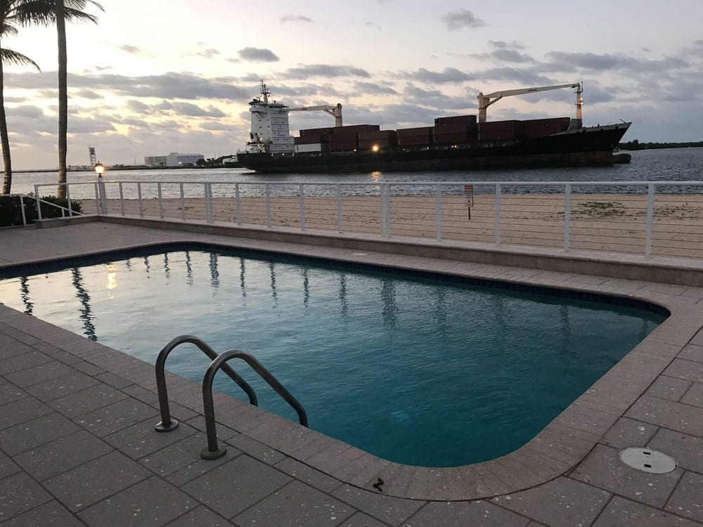 Rounded rectangle pool near the ocean with a cargo ship passing by