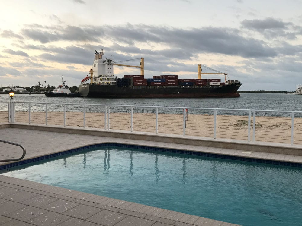 Rounded rectangle pool near the ocean with a cargo ship passing (cloudy)