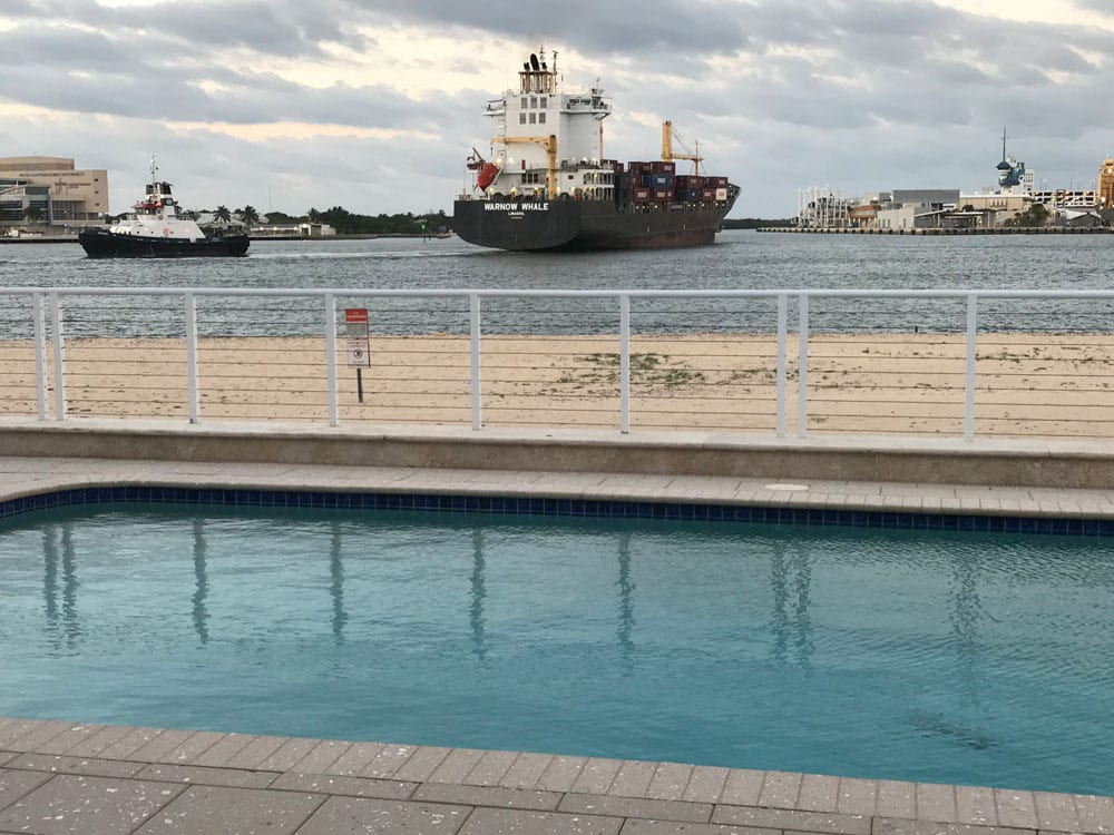 Rounded rectangle pool near the ocean with a black cargo ship in the background