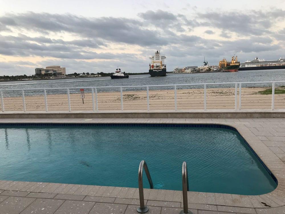 Rounded rectangle pool near the ocean with a black cargo ship sailing away toward the horizon
