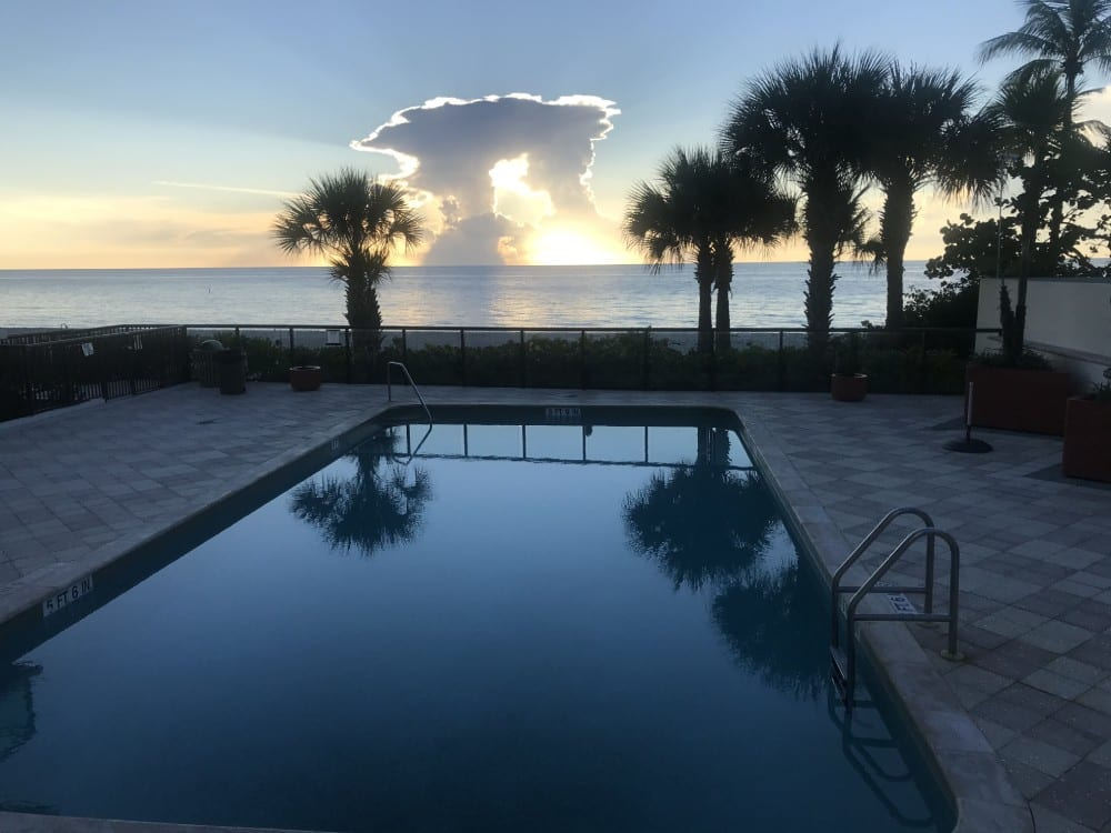 A pool near the beach during a sunset with cloud formations in the background