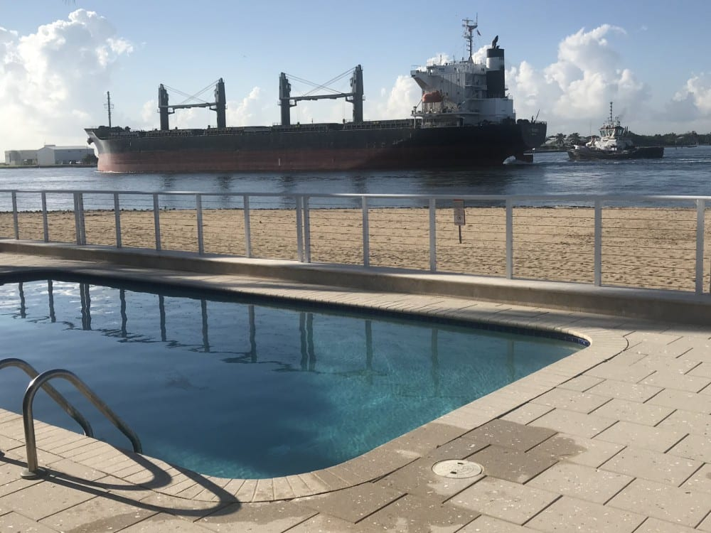 Rounded rectangle pool near the ocean and a new cargo ship in the background (sunny)