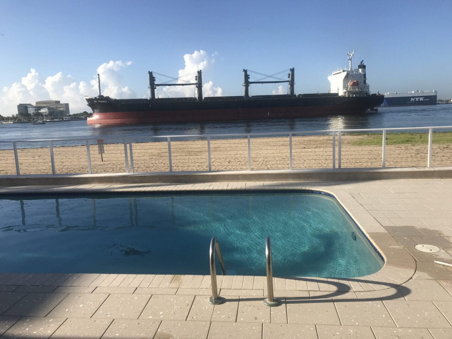 Rounded rectangle pool near the ocean and a big ship nearby (different angle)