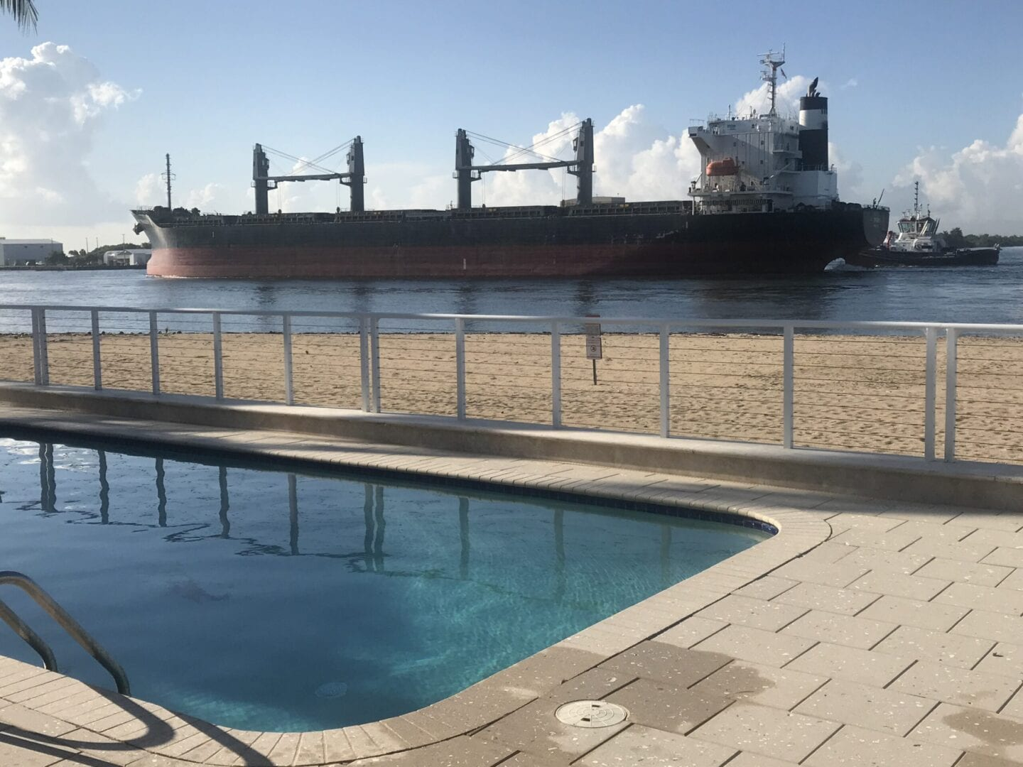 Rounded rectangle pool near the ocean and a big ship nearby