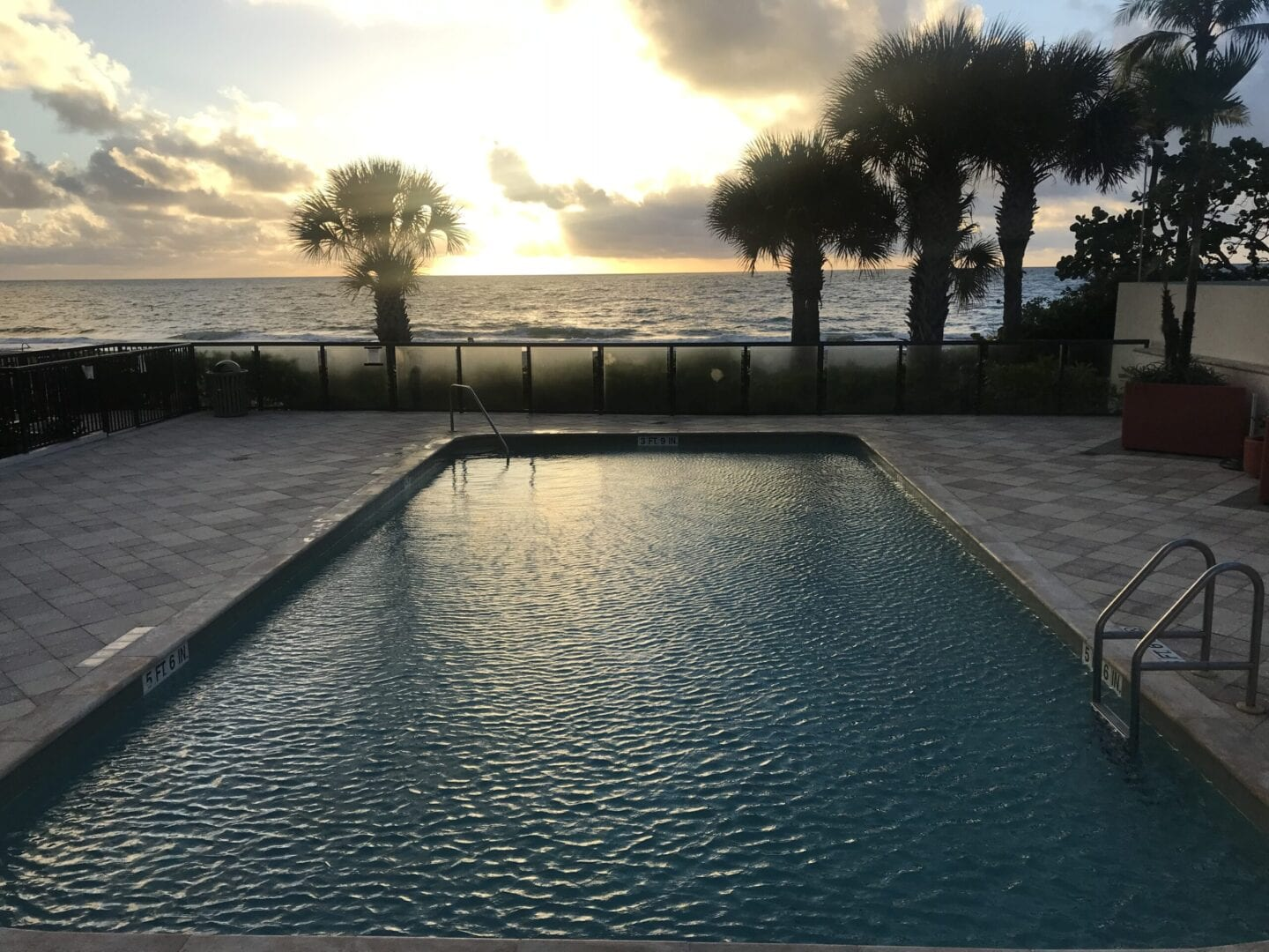 Pool near the beach enclosed by a black fence and frosted glass