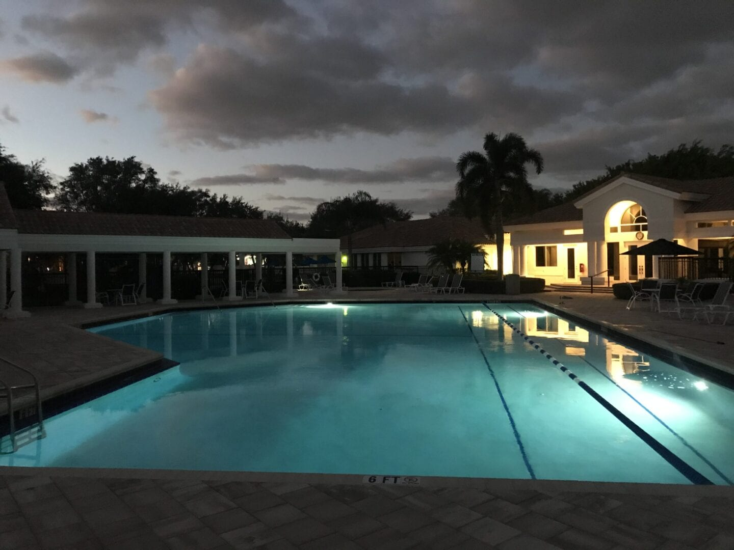 Pool with pool rope surrounded by white outdoor patios and a white house (at night)
