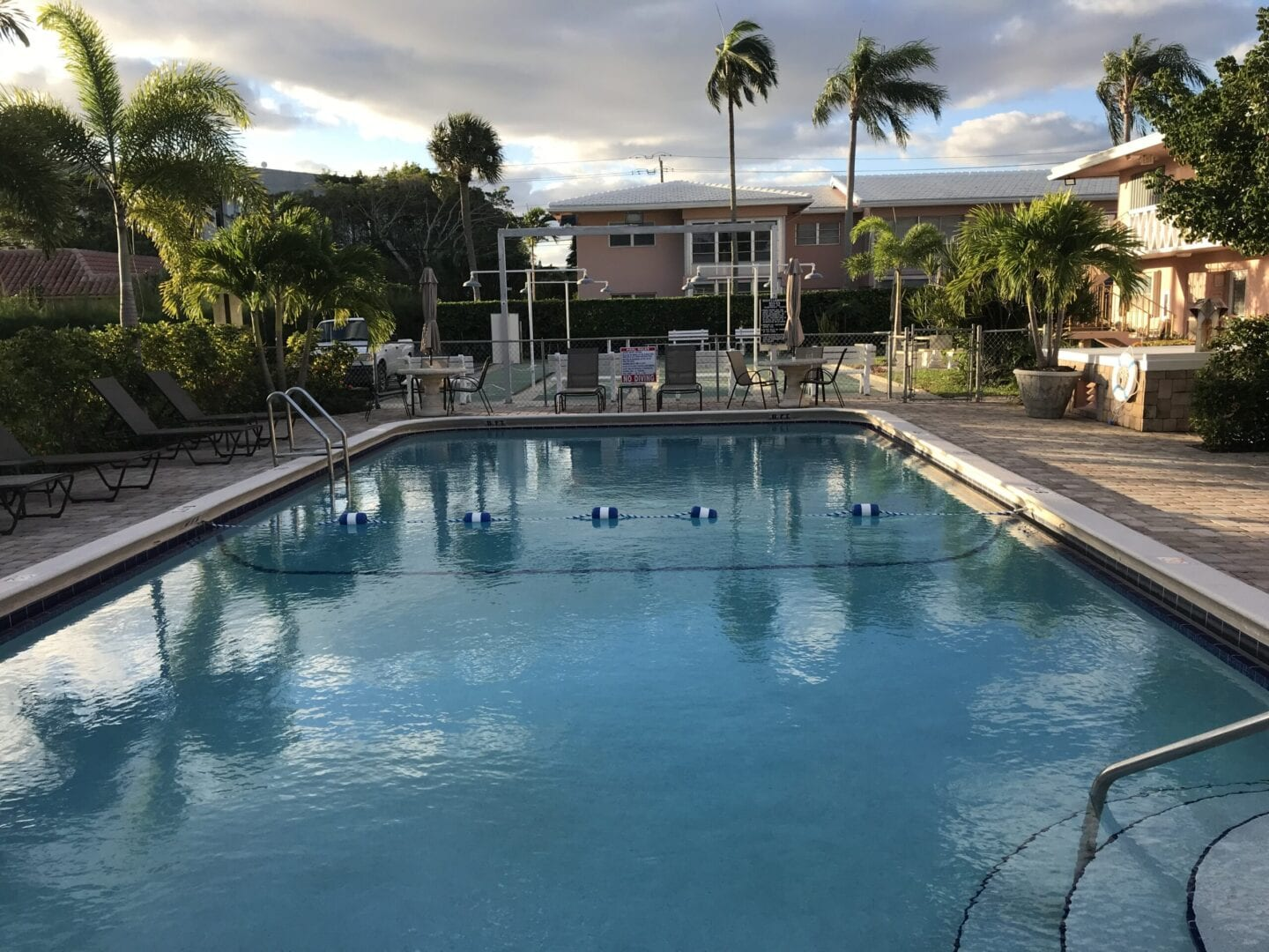 Rounded rectangle pool with a pool safety rope behind houses and palm trees