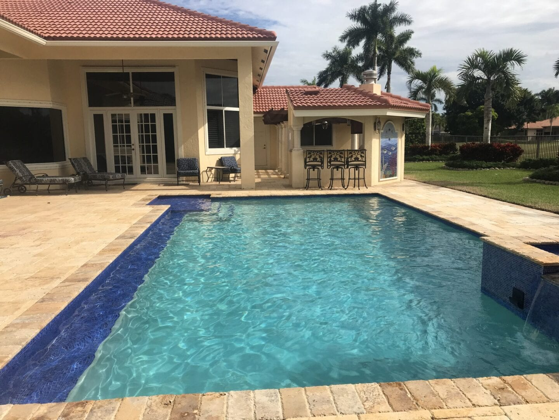 Pool in the backyard of a beige house