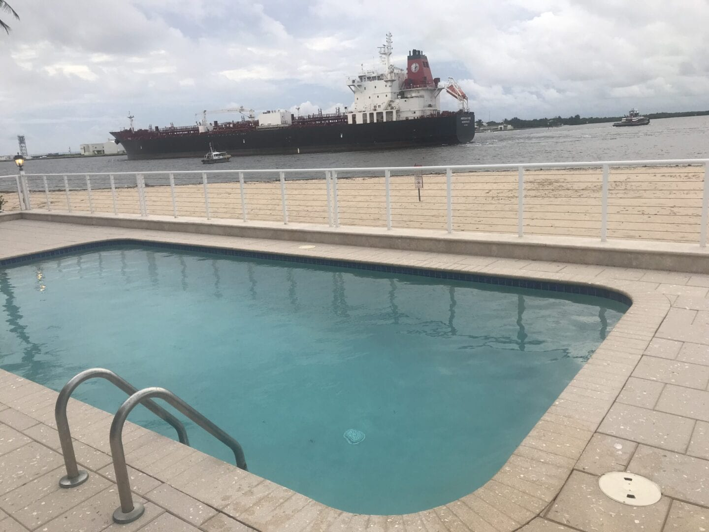 Rounded rectangle pool near the ocean with a ship passing by