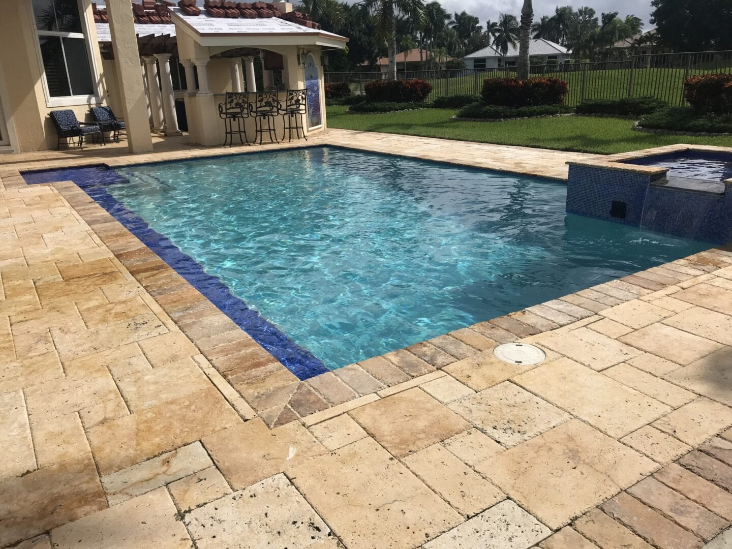 Pool in the backyard of a beige house (slanted view)
