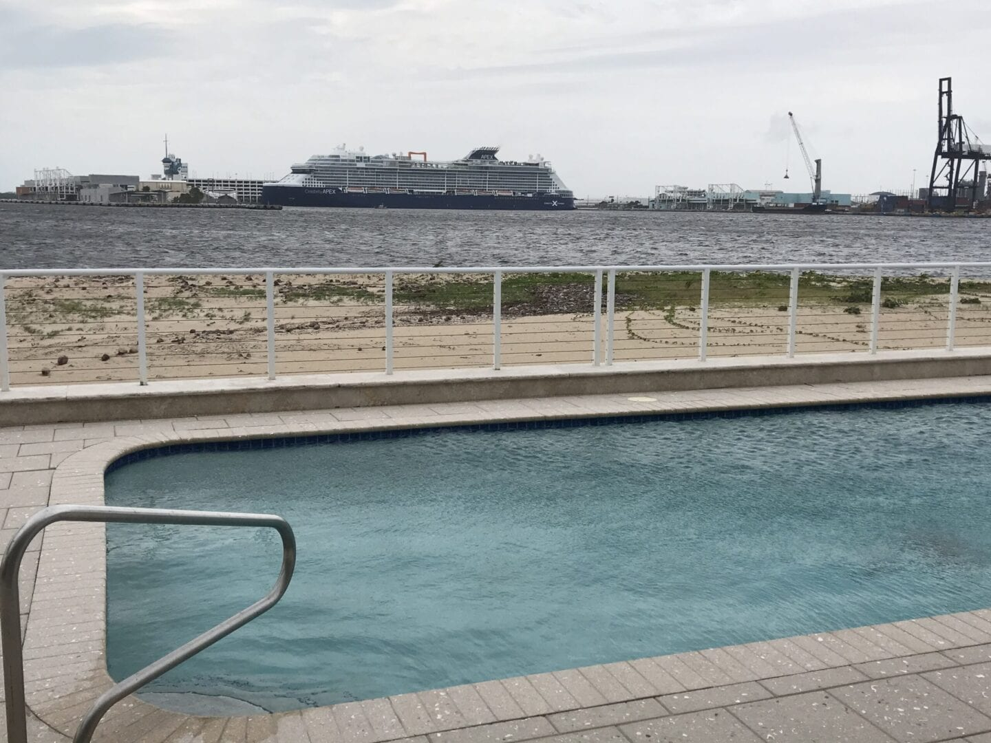 Rounded rectangle pool (different angle) near the ocean with a cruise ship passing by