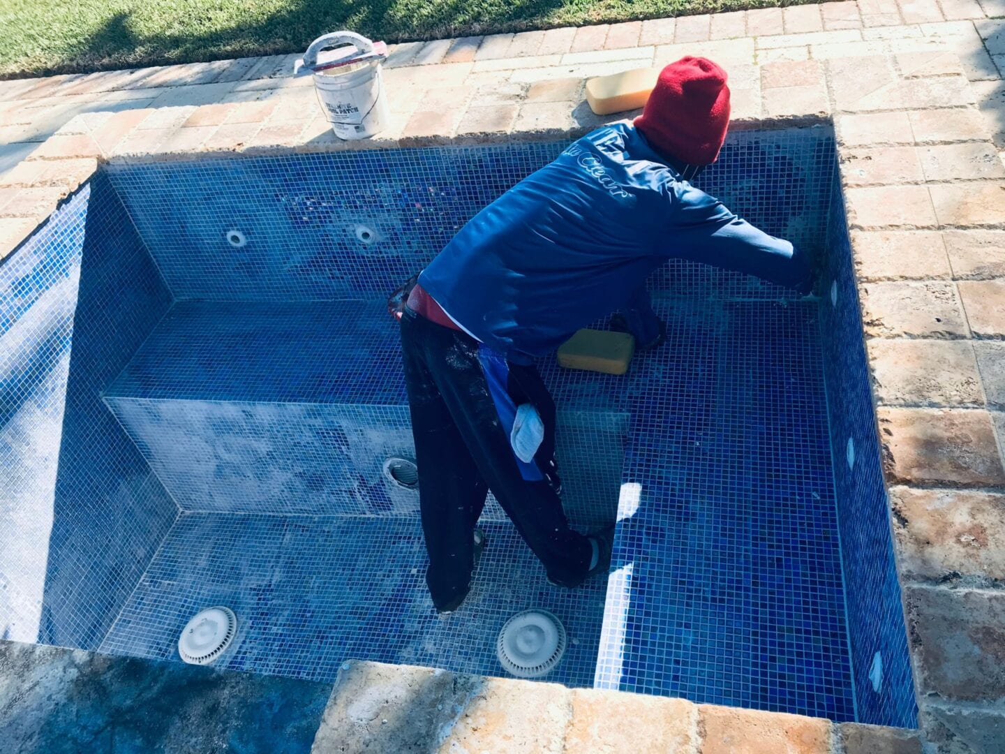Man with red bonnet scrubbing the tiles of a pool