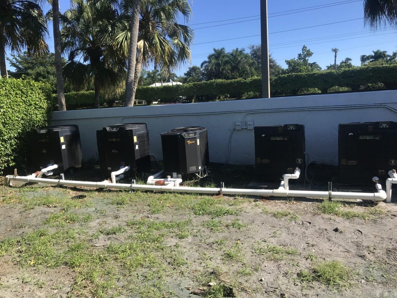 Five black pool heat pumps and equipment