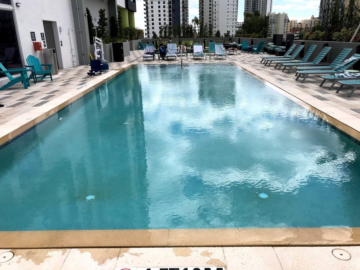 Rectangle pool surrounded by pool chairs with tall buildings in the background