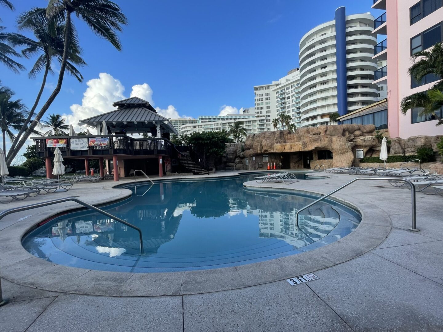 A curvy pool surrounded by several buildings