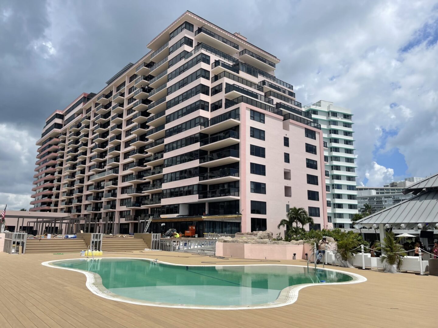 A curvy pool on wooden floors with a tall, beautiful building in the background
