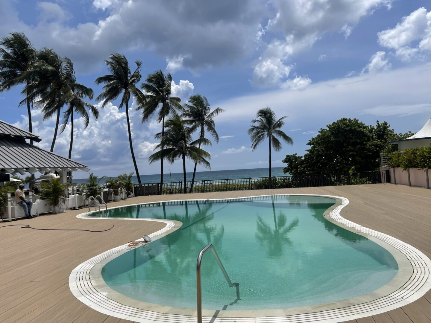 Small, curvy pool with floor tiles and palm trees and the beach in the background (landscape; afternoon)