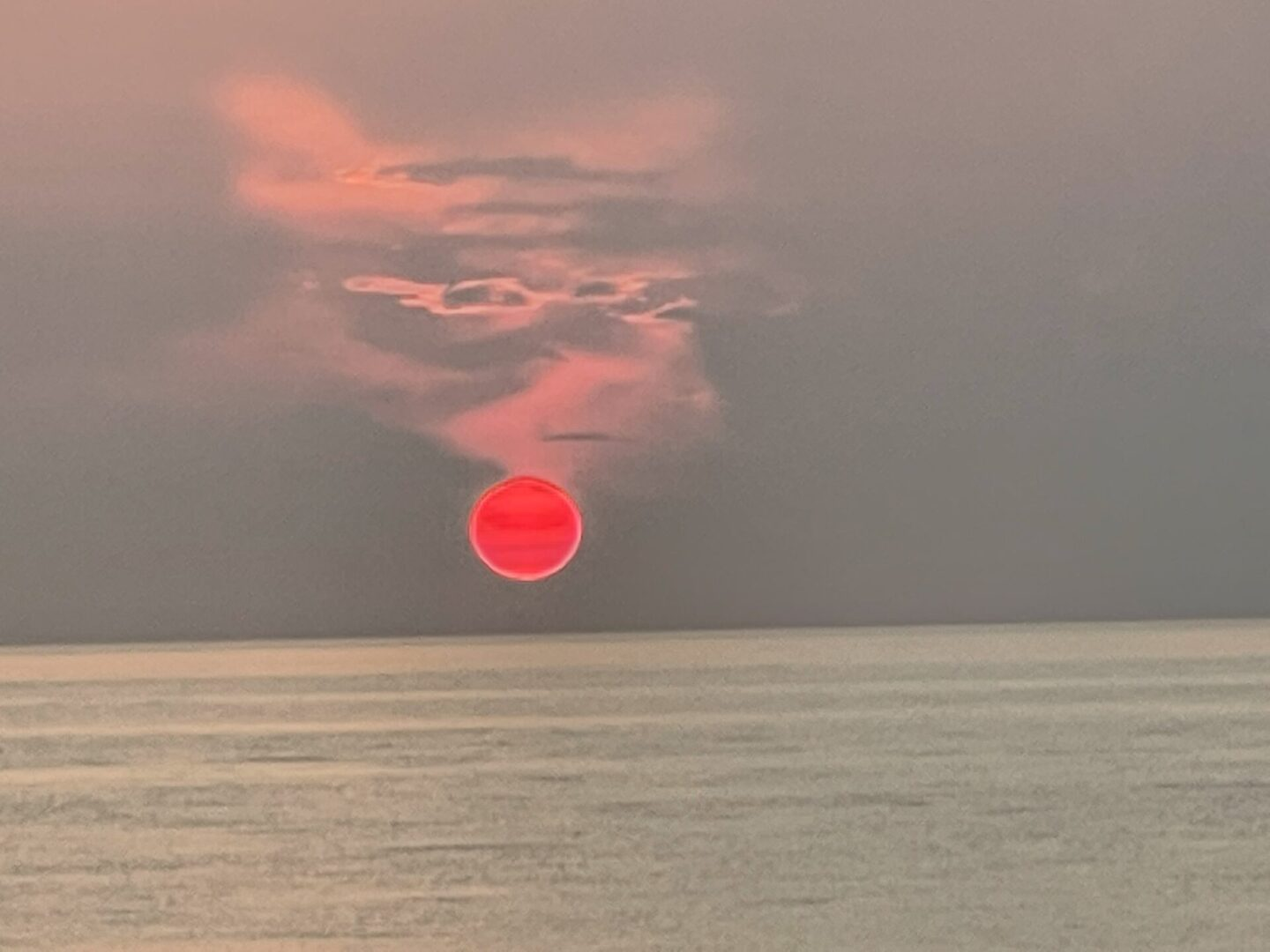 A red sun setting on the horizon