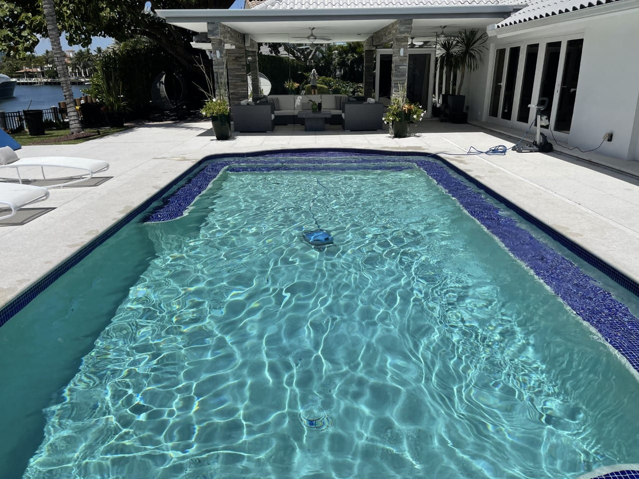 Rectangular pool with a white patio in front and white pool chairs on one side