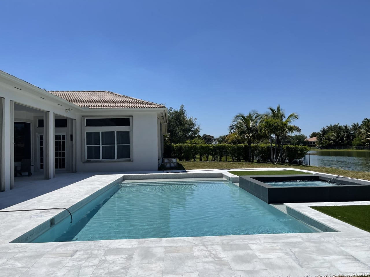 Classy rectangular pool on a white tiled floor and a white house on the left side